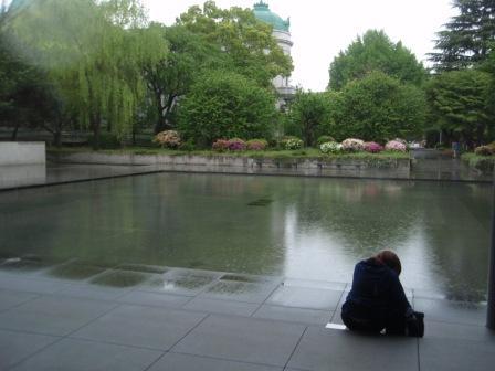 小雨の中、法隆寺宝物館前の庭園に一人佇む娘