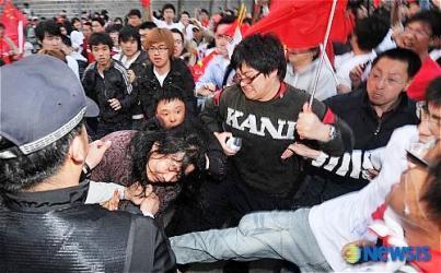 年配のチベット人女性を襲撃する中国人