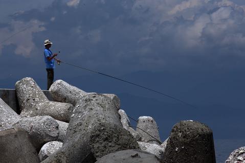 梅雨の雲と釣り人