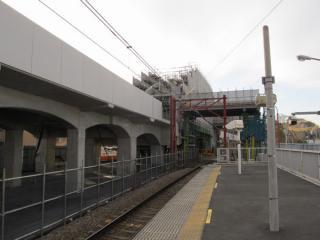 架設中のアーチ橋を地上ホームから見る。