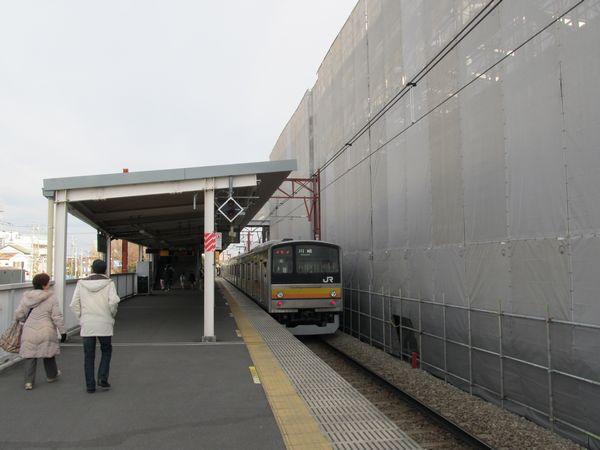 南多摩駅の地上ホーム。ネットの裏で高架橋本体の建設が進む。