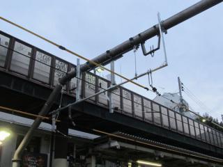 架線柱は従来のものを流用しており、線路の位置が下がった分アダプターで穴埋めしている。
